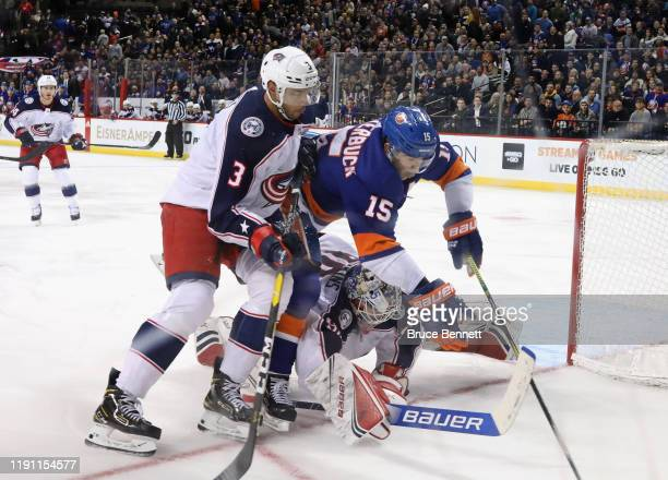 Seth Jones and Elvis Merzlikins of the Columbus Blue Jackets defend against Cal Clutterbuck of the New York Islanders at the Barclays Center on...
