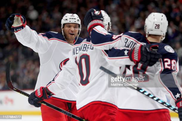 Seth Jones and Oliver Bjorkstrand of the Columbus Blue Jackets celebrate a goal by Alex Wennberg against the Colorado Avalanche in the third period...