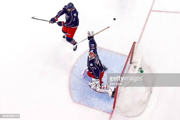 Seth Jones of the Columbus Blue Jackets moves out of the way of a shot as Sergei Bobrovsky of the Columbus Blue Jackets deflects the puck back over...