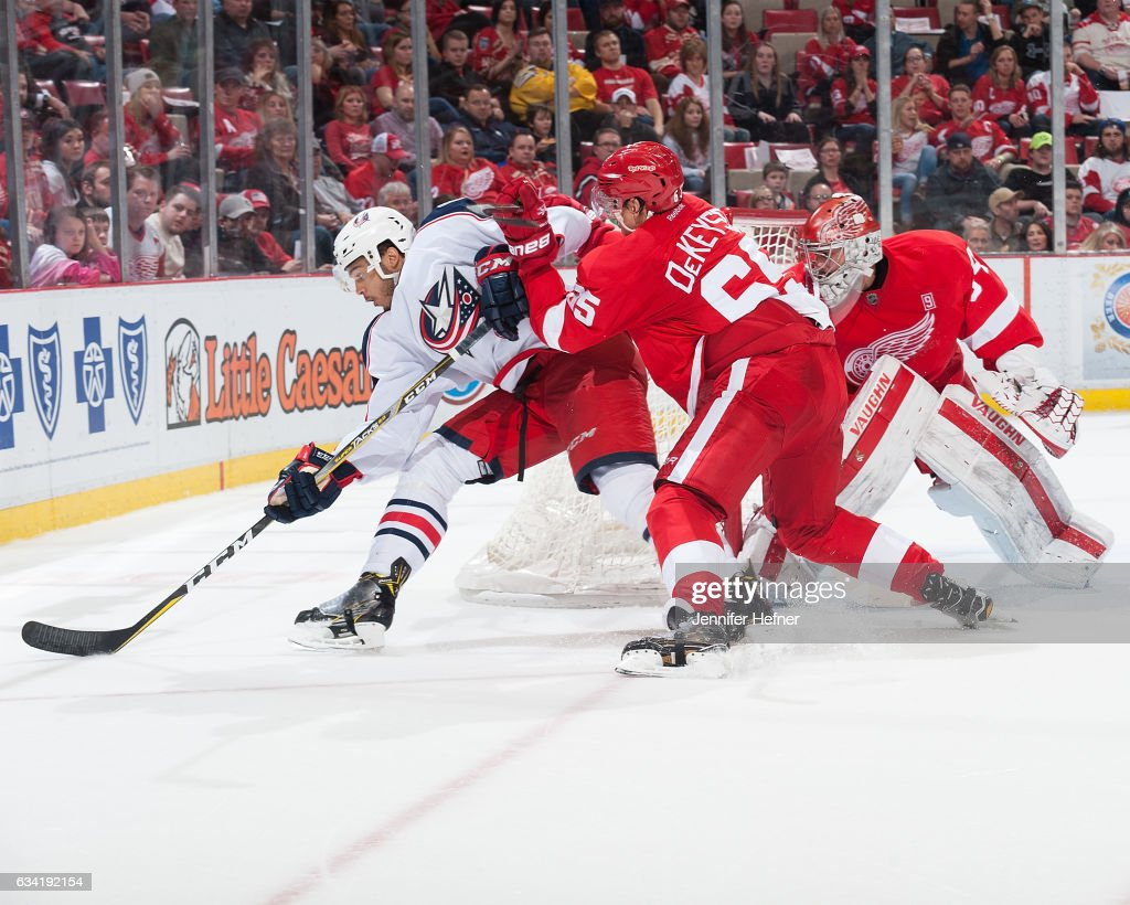 Seth Jones #3 of the Columbus Blue Jackets tries to protect the puck as Danny DeKeyser #65 of the Detroit Red Wings defends him to the side of the net during an NHL game at Joe Louis Arena on February 7, 2017 in Detroit, Michigan.
