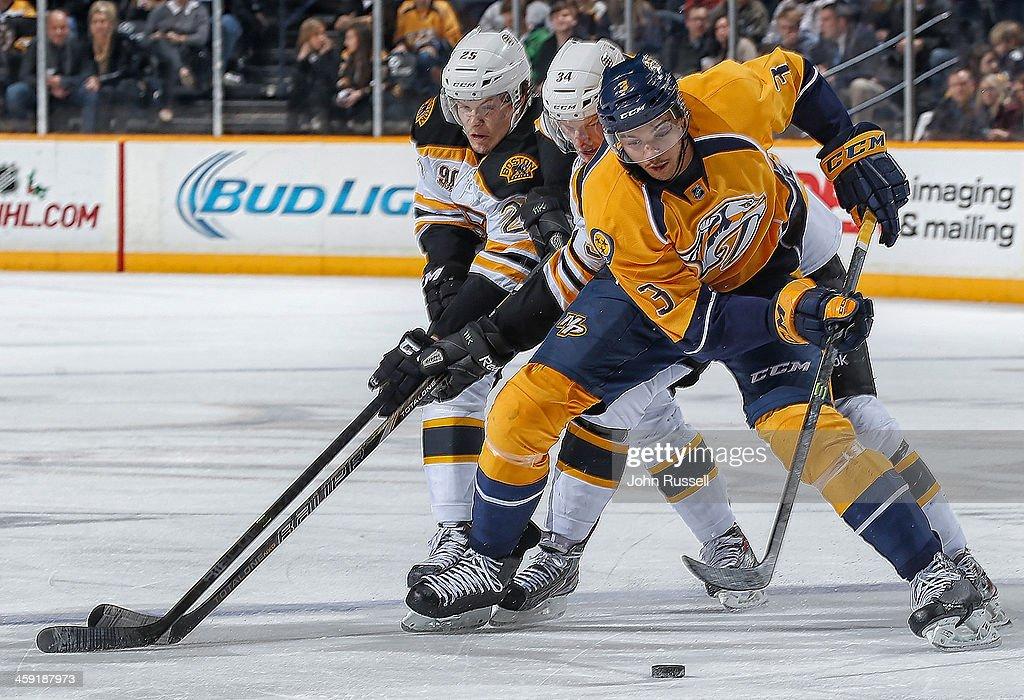 Seth Jones #3 of the Nashville Predators skates the puck into the zone against Matt Fraser #25 and Carl Soderberg #34 of the Boston Bruins at Bridgestone Arena on December 23, 2013 in Nashville, Tennessee.