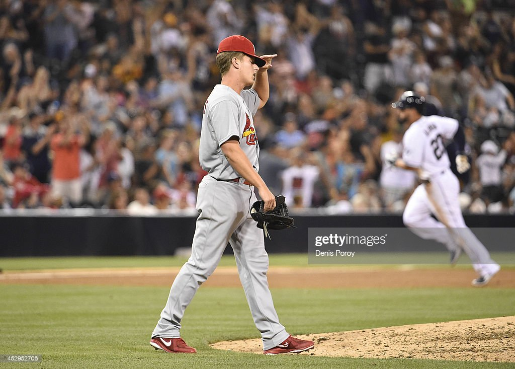Seth Maness #61 of the St. Louis Cardinals walks back to the mound after giving up a three-run home run to Will Venable #25 of the San Diego Padres as Yonder Alonso #23 rounds the bases during the seventh inning of a baseball at Petco Park July 30, 2014 in San Diego, California.