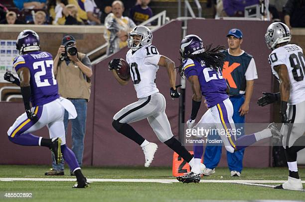 Seth Roberts of the Oakland Raiders carries the ball against Shaun Prater and Trae Waynes of the Minnesota Vikings during the preseason game on...