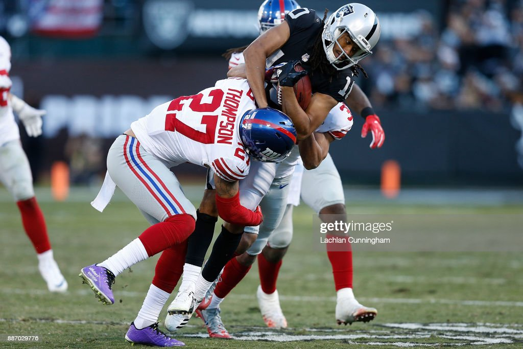 Seth Roberts #10 of the Oakland Raiders is tackled by Darian Thompson #27 and Ross Cockrell #37 of the New York Giants at Oakland-Alameda County Coliseum on December 3, 2017 in Oakland, California.