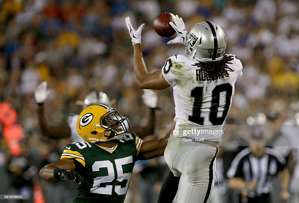 Seth Roberts #10 of the Oakland Raiders makes a catch past Marwin Evans #25 of the Green Bay Packers in the third quarter of a preseason game at Lambeau Field on August 18, 2016 in Green Bay, Wisconsin.