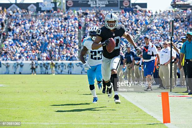 Seth Roberts of the Oakland Raiders runs the ball in for a touchdown while being chased by Brice McCain of the Tennessee Titans at Nissan Stadium on...