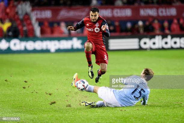Seth Sinovic of Sporting Kansas City performs a sliding tackle on Steven Beitashour of Toronto FC during the second half of the MLS Soccer regular...