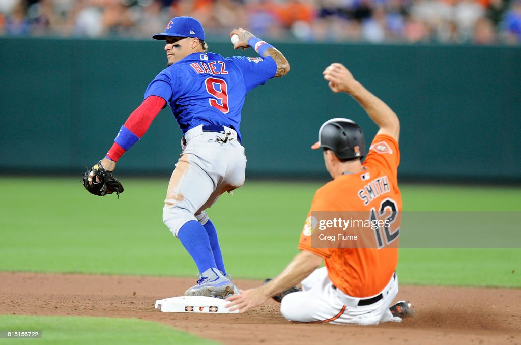 Seth Smith #12 of the Baltimore Orioles is forced out at second base in the seventh inning by Javier Baez #9 of the Chicago Cubs at Oriole Park at Camden Yards on July 15, 2017 in Baltimore, Maryland.