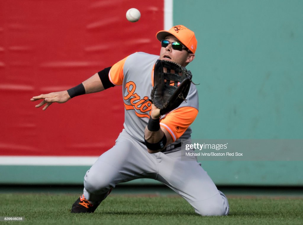 Seth Smith #12 of the Baltimore Orioles makes a catch against Eduardo Nez #36 of the Boston Red Sox in the eighth inning at Fenway Park on August 27, 2017 in Boston, Massachusetts.