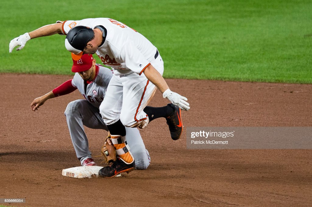 Seth Smith #12 of the Baltimore Orioles slides safely under the tag of Andrelton Simmons #2 of the Los Angeles Angels of Anaheim for a seventh inning double during a game at Oriole Park at Camden Yards on August 19, 2017 in Baltimore, Maryland.