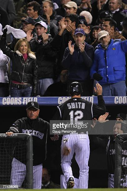 Seth Smith of the Colorado Rockies is congratulated by manager Clint Hurdle after Smith scored on a RBI single by Kazuo Matsui in the bottom of the...