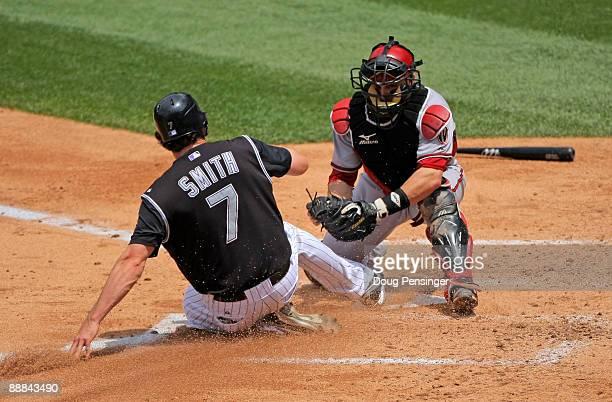 Seth Smith of the Colorado Rockies slides under the tag of catcher Miguel Montero of the Arizona Diamondbacks to score on a Todd Helton single in the...