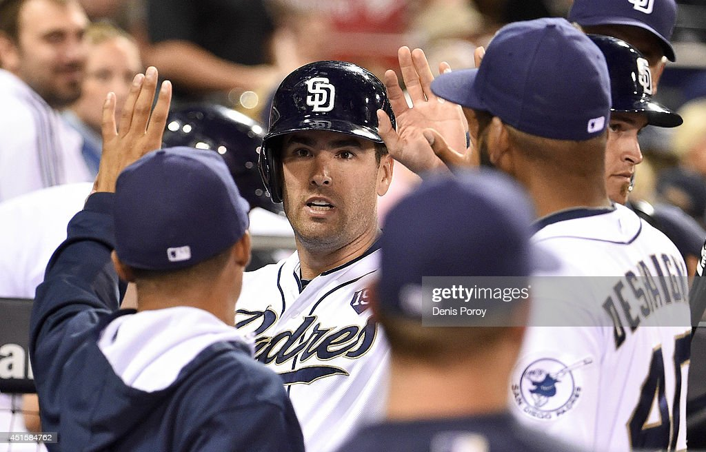 Seth Smith #12 of the San Diego Padres is congratulated after scoring during the fifth inning of a baseball game against the Cincinnati Reds at Petco Park July 1, 2014 in San Diego, California.