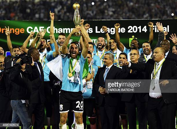 ES Setif captain Farid Mellouli holds the CAF Champions League trophy on November 1 2014 in the MustaphaTchaker stadium in Blida as his team mates...