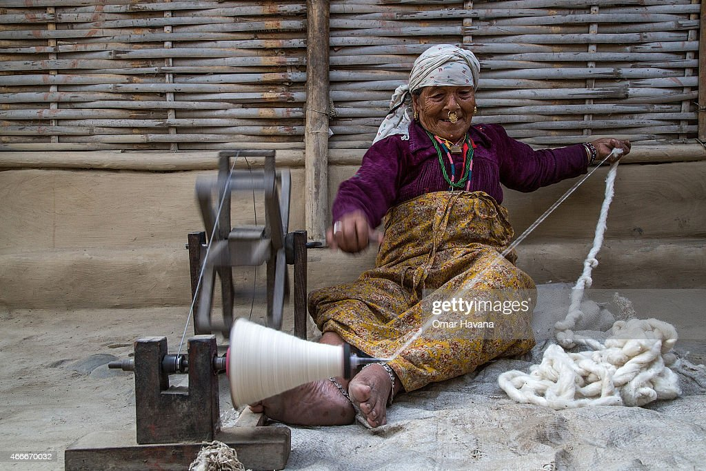 Setimaya Tamang, 76 years old, rolls wool outside her home in the Beldangi 1 refugee camp on March 13, 2015 in Beldangi, Nepal. More than 18,000 Bhutanese refugees still reside in the refugee camps set up in Nepal in the 1990s, after hundreds of thousands of Bhutanese fled the country following a campaign of ethnic cleansing by the Bhutanese Government against the country's ethnic Nepali population. After more than 20 years in Nepal, over 90% of the refugees have been successfully resettled in third countries, thanks to programs by UNHCR and IOM. Those remaining the camps are supported by several organizations that undertake a wide variety of projects. Helped by remittances sent back to Nepal by families already resettled in other countries, the refugees still in the camps have set up their own small businesses in the camps and the roads near them, roads which are also replete with Nepali-owned businesses who benefit directly from the refugees that are still waiting in Nepal to be resettled in third countries. (Photo by Omar Havana/Getty Images).