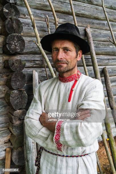 seto man (indigenous ethnic and linguistic orthodox christian minority in se estonia), in traditional dress by his traditional wooden house, nr miku, setomaa, se estonia (model release) - traditionele kledij stockfoto's en -beelden