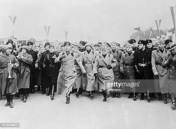 Setting an example for his admiring staff Premiere Benito Mussolini of Italy is shown here doing the goose step Germany's ceremonial military march...