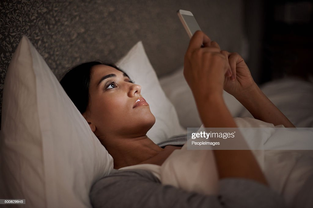 Setting her alarm for an early wake up : Stock Photo