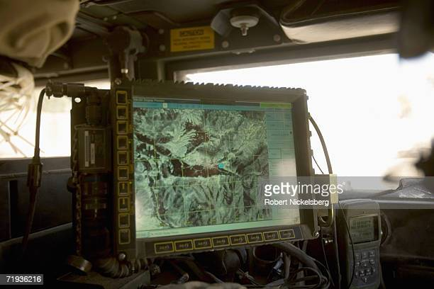Setting off on a local battle damage assessment, a US Army soldier, not shown, refers to his position on a topographic map from a Blue Force Tracker...
