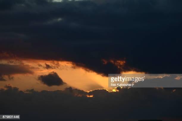 Setting sun behind dark clouds