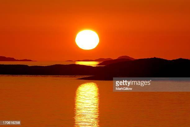 Setting sun in bright orange sky over water