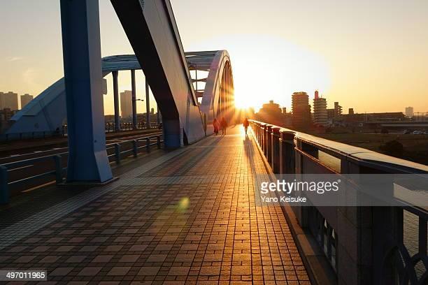 setting sun on a bridge - 背景に人 ストックフォトと画像