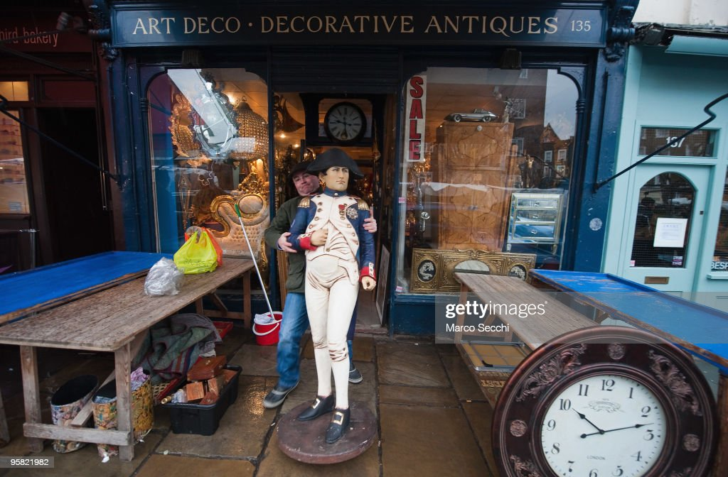 Setting up for Saturday trade at one of the antique shops it Portobello Road on January 16, 2010 in London, England. Portobello traders fear for the Market's future after Lipka's Antiques Arcade, where more than 150 traders had their stalls, was redeveloped to accommodate a large High street chain store.