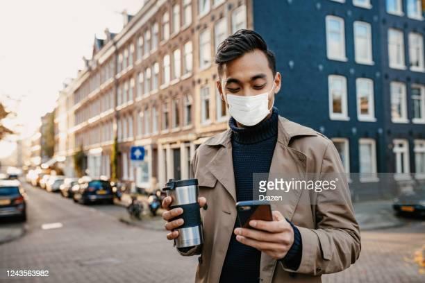 opzetten van online zakelijke bijeenkomst met gezichtsmasker op tijdens coronavirus - noord holland stockfoto's en -beelden