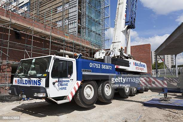 Setting up outriggers for a tall mobile crane on a construction site