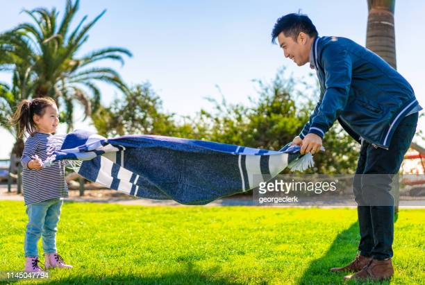 setting up the picnic rug together - picnic blanket stock pictures, royalty-free photos & images