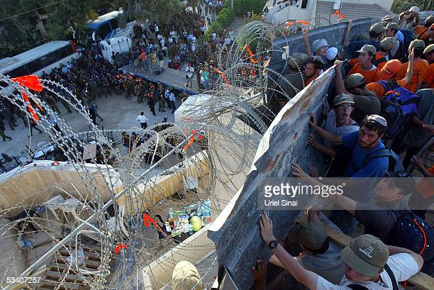 Settler activists and extremists battle with riot police while on the synagogue roof during the evacuation August 18 2005 of the veteran Gaza Strip...