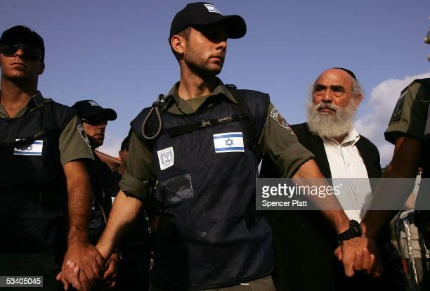 A settler peers out over military police officers August 18 2005 the Israeli settlement of Neve Dekalim in the Gush Katif block of Settlements in...