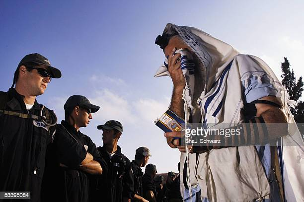 A settler prays in front of riot police after they forced their way in through the front gate of the largest Jewish settlement August 16 2005 Neve...