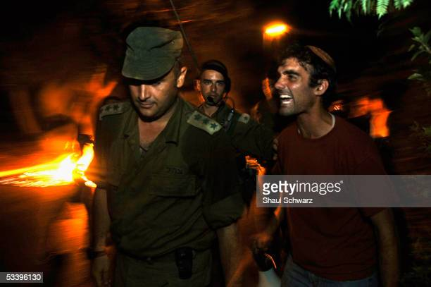 A settler screams at a solider as the Israeli army officers deliver the eviction notice to a Jewish settler late on August 16 2005 in the Gaza Strip...