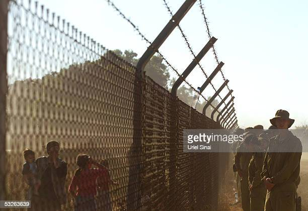 Settler supporters and Israeli soldiers stand on opposite sides July 20 separated by a fence surrounding the Israeli town of Kfar Maymon Thousands...