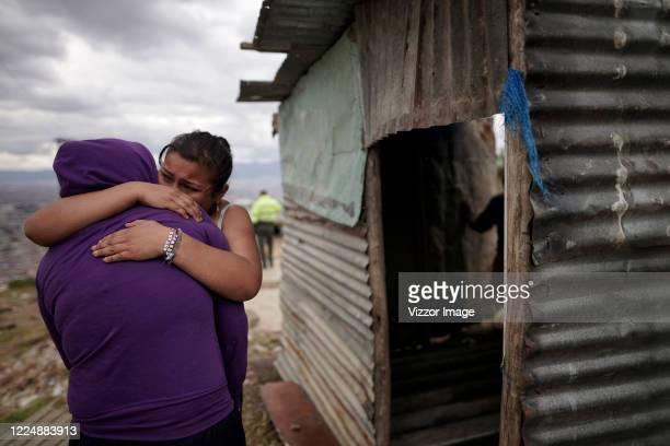 Settlers about to be evicted hug at Los Altos de La Estancia neighborhood on May 14, 2020 in Bogota, Colombia. Today the last of 200 families who had...