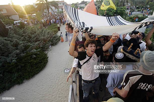 Settlers shout as they carry a prayer shawl over a newly dedicated Torah scroll in the southern Gaza Strip settlement of Neve Dekalim 16 August 2005...