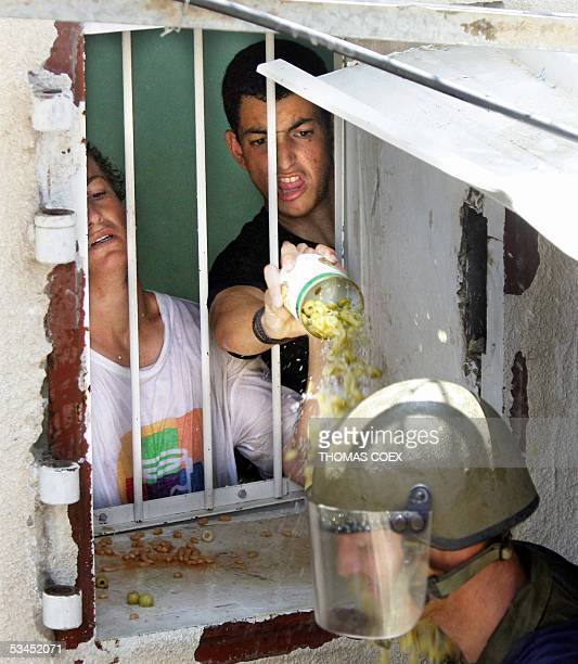 Settlers throw a can of olives on an Israeli soldier during the evacuation of the West Bank settlement of Homesh 23 August 2005 Israel security...