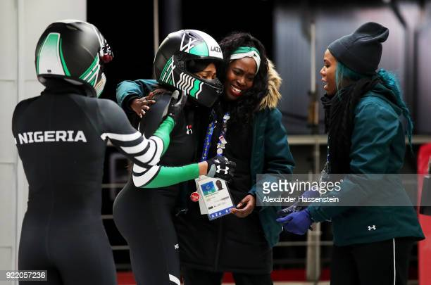 Seun Adigun and Akuoma Omeoga of Nigeria react with Aminat Odunbaku in the finish area during the Women's Bobsleigh heats on day twelve of the...