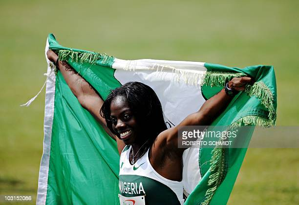 Seun Adigun of Nigeria celebrates with the Nigerian flag after crossing the finish line in first place in the Women's 100 metres Hurdles final during...