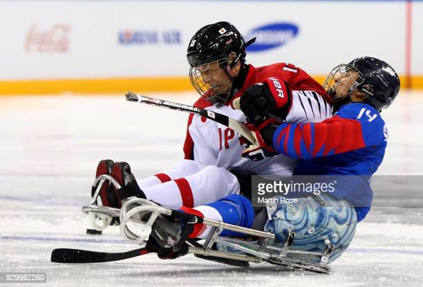 Seung Hawn Jung of Korea battles for the puck with Mamoru Yoshikawa of Japan in the Ice Hockey Preliminary Round Group A game between South Korea and...