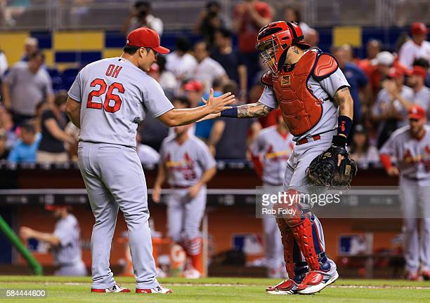 Seung Hwan Oh of the St Louis Cardinals shakes hands with Yadier Molina after defeating the Miami Marlins 54 at Marlins Park on July 28 2016 in Miami...