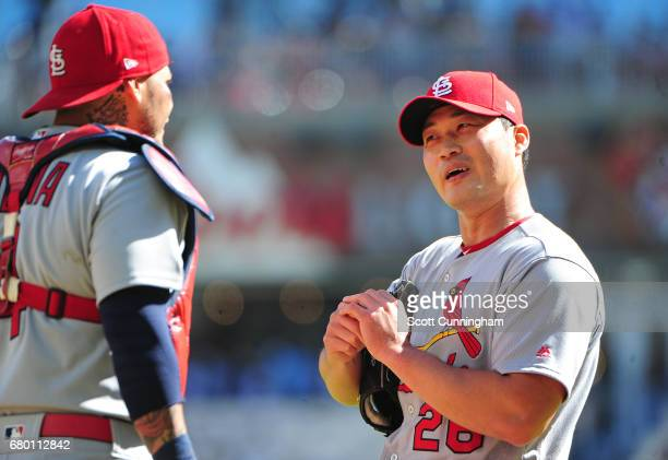 Seung Hwan Oh of the St Louis Cardinals talks with Yadier Molina during the 11th inning against the Atlanta Braves at SunTrust Park on May 7 2017 in...