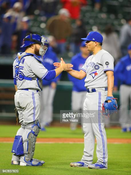 Seung Hwan Oh of the Toronto Blue Jays is congratulated by Russell Martin for closing out the game for the win against the Texas Rangers at Globe...