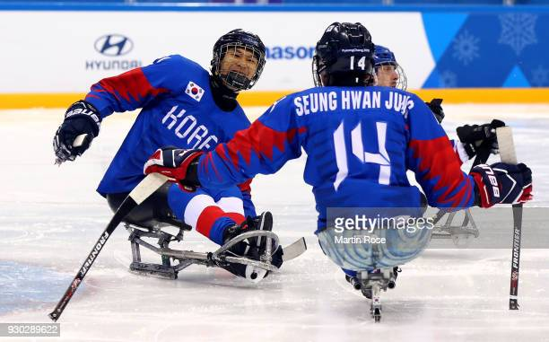Seung Ju Lee of Korea celebrate with team mate Seung Hawn Jung the opening goal in the Ice Hockey Preliminary Round Group B game between Korea and...
