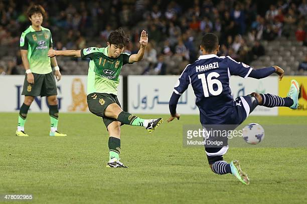 Seunggi of Joenbuk kicks the ball past Rashid Mahazi of the Victory during the AFC Asian Champions League match between the Melbourne Victory and...