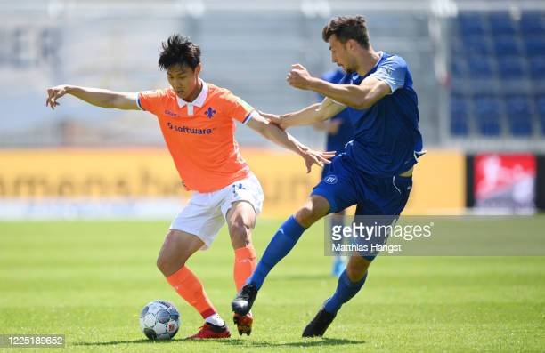 Seung-ho Paik of Darmstadt is challenged by Lukas Froede of Karlsruhe during the Second Bundesliga match between Karlsruher SC and SV Darmstadt 98 at...