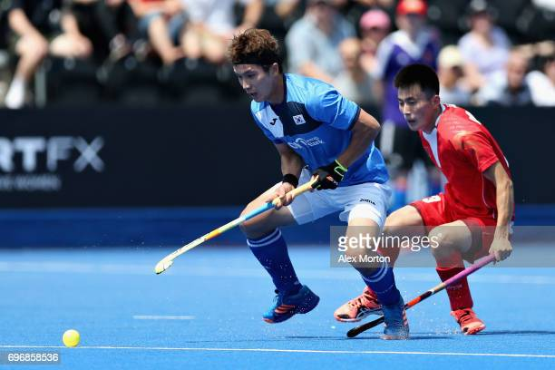 Seunghoon Lee of South Korea battles for the ball with Zixiang Gou of China during the Hero Hockey World League Semi Final match between China and...