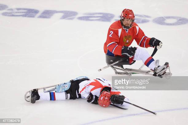 SeungHwan Jung of Korea lies down after being checked by Aleksei Lysov of Russia during the Ice Sledge Hockey Preliminary Round Group A match between...