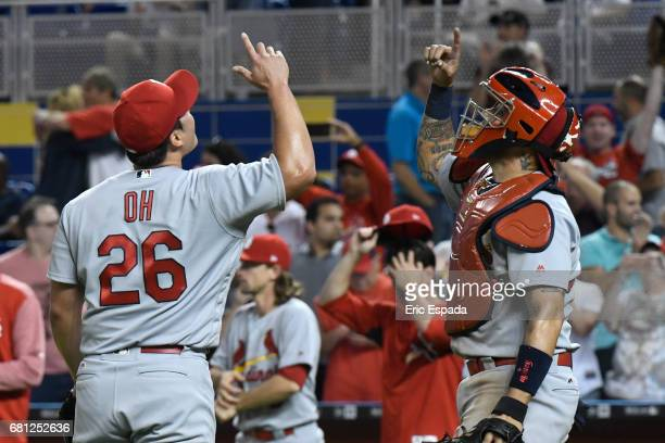 SeungHwan Oh and Yadier Molina of the St Louis Cardinals point to the sky after beating the Miami Marlins at Marlins Park on May 9 2017 in Miami...
